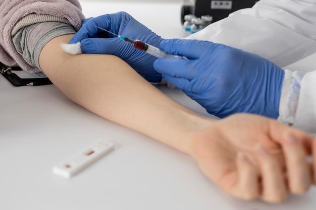 Medico del primo piano che preleva un campione di sangue da un paziente