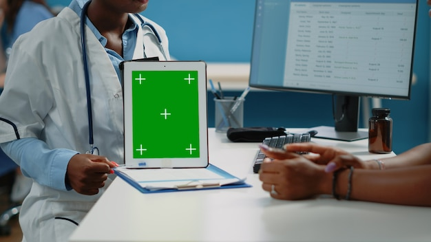 Primo piano del medico che tiene in verticale il tablet con lo schermo verde