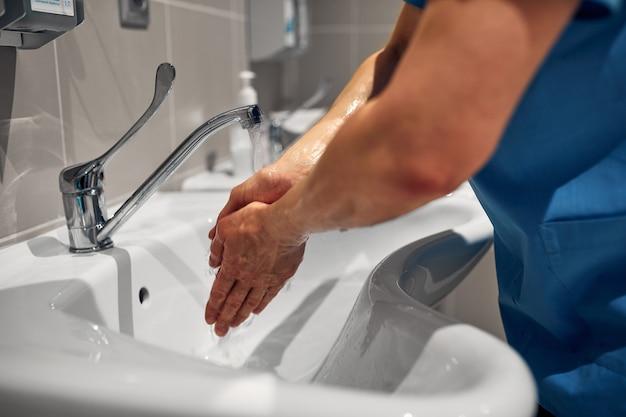 Primo piano di un medico che si lava le mani usando un dispenser di disinfettante..