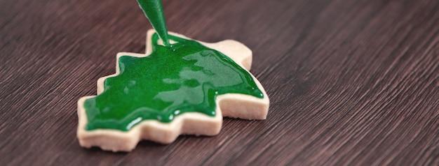 Chiuda in su del biscotto di zucchero dell'albero di natale del pan di zenzero del disegno sul fondo di legno della tavola con la glassa verde, concetto della celebrazione di festa.