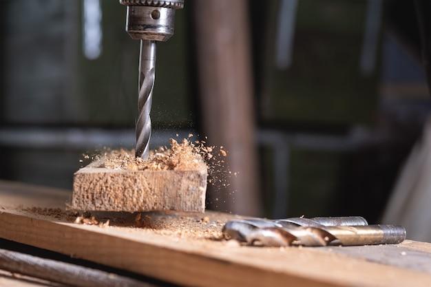 Primo piano del trapano in movimento durante la foratura del legno in officina