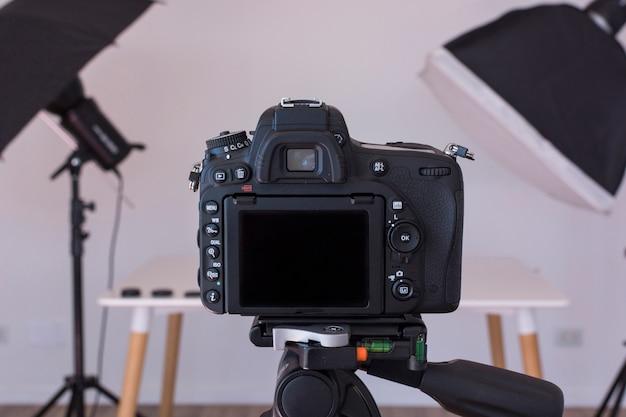 Primo piano della macchina fotografica del dslr su un treppiede nello studio della foto