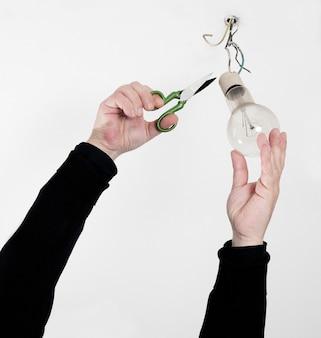 Primo piano delle mani dell'elettricista e una lampadina