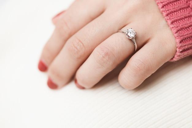Primo piano di un elegante anello di diamanti di fidanzamento sul dito della donna con vestire inverno maglione rosa.