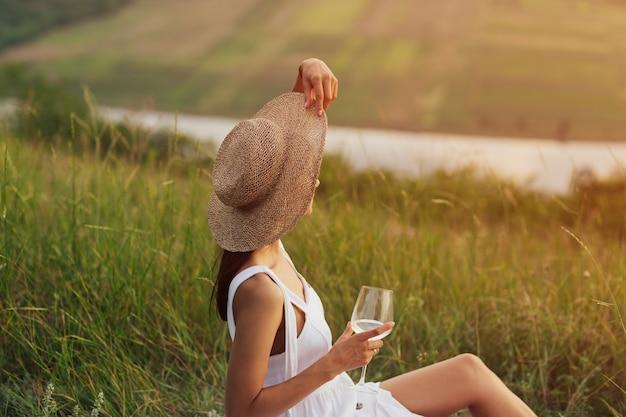 Primo piano di una ragazza elegante in abito bianco e cappello di paglia con un bicchiere di vino in mano sta facendo un picnic in natura.