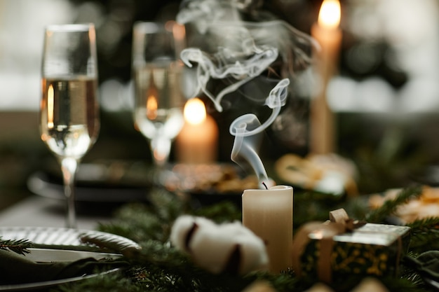 Primo piano di un'elegante candela bianca sul tavolo da pranzo di natale con lo spazio della copia ondeggiante del fumo