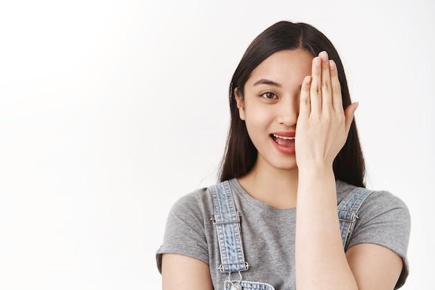 Primo piano emotiva carina ragazza asiatica prova un nuovo prodotto cosmetico pelle incline all'acne mostra prima di chiudere metà faccia con risultato sorridente gioiosamente combattendo una cattiva condizione della pelle determinata vincere muro bianco