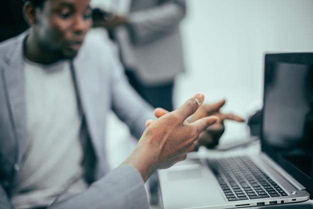 Avvicinamento. dipendenti che guardano lo schermo del laptop. sfondo di affari