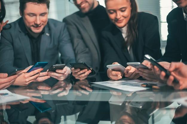 Avvicinamento . dipendenti con smartphone seduti alla scrivania. persone e tecnologia