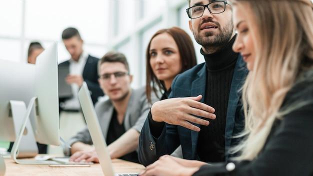 Close up dipendenti lavorano su laptop in un ufficio moderno