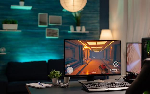 Primo piano di uno studio domestico di gioco vuoto con luci al neon dotate di computer potente professionale, cuffie, parola chiave rgb, mouse