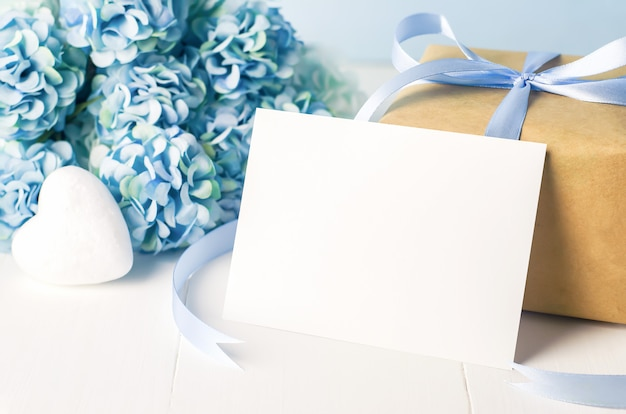 La fine su della cartolina d'auguri bianca vuota con marrone ricicla il contenitore di regalo ed i fiori blu dell'ortensia