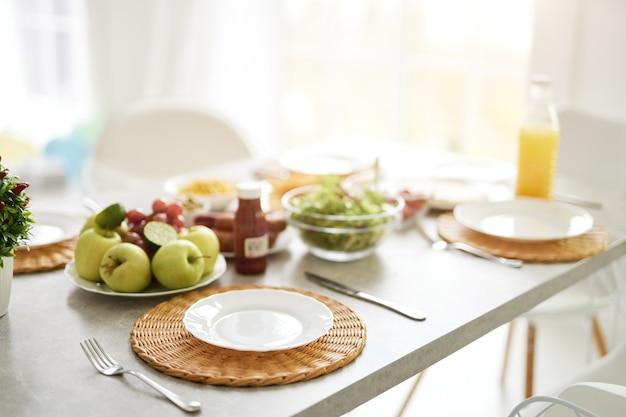 Primo piano del piatto bianco vuoto e colazione in stile latino sul tavolo. interno bianco luminoso moderno della cucina con i dettagli di legno e bianchi. mattina, concetto di idee per la colazione. messa a fuoco selettiva