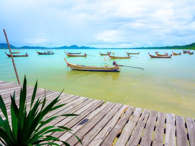 Chiuda sul molo di legno vuoto con barche di pescatori locali sullo sfondo del cielo e del mare in thailandia.