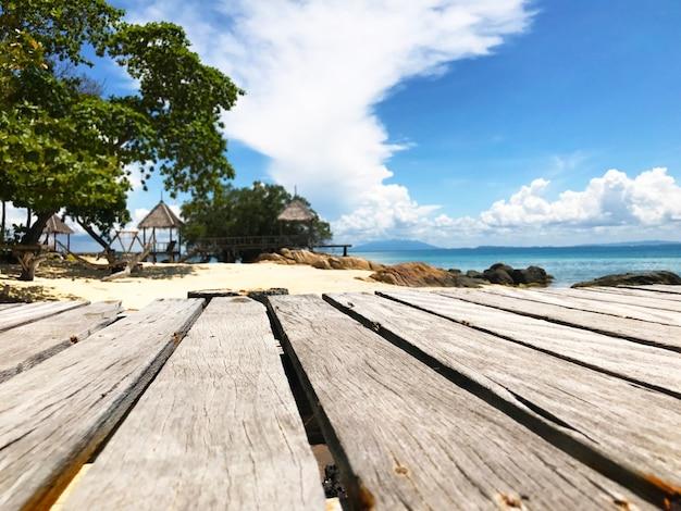 Chiuda sul ponte vuoto della plancia di legno sullo sfondo del cielo e del mare in una giornata di sole.