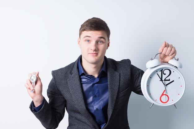 Close up energico giovane imprenditore tenendo sveglia e orologio da polso mentre si guarda la telecamera. isolato su sfondo bianco.