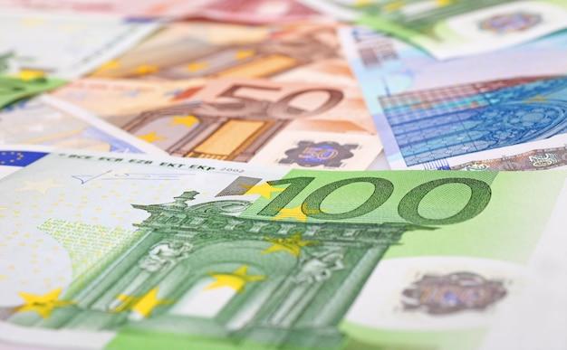 Primo piano su banconote e monete in euro sulla tavola di legno