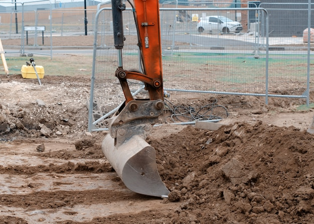 Primo piano di una benna di un escavatore posto a terra in posizione sicura