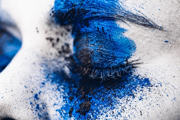 Primo piano dell'occhio della ragazza del modello di moda con trucco colorato in polvere.