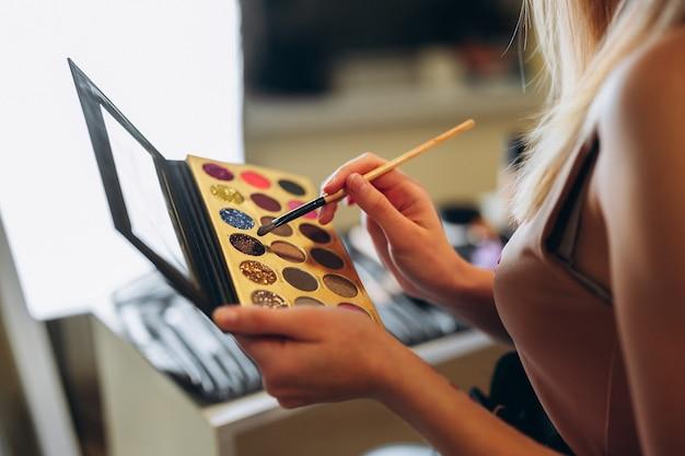 Primo piano di ombretti in diversi colori e glitter che vengono applicati a pennello. palette di ombretti neri con ombretto multicolore e uno specchio nelle mani di una donna.