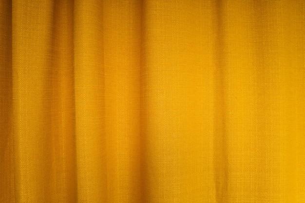 Primo piano di tende in tessuto giallo con pieghe. sfondo astratto, tenda, drappeggi in tessuto dorato.