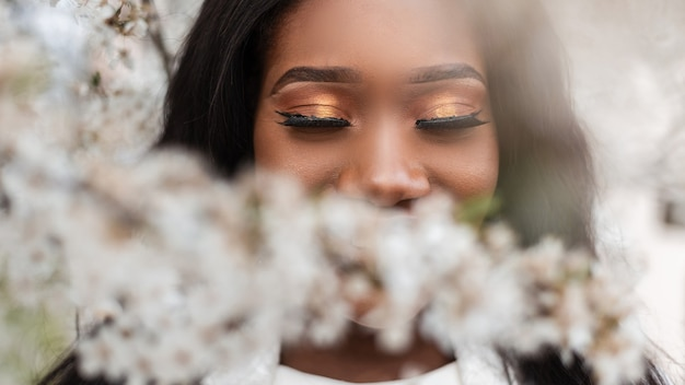 Fronte ravvicinato di una bella donna di colore africana felice con gli occhi chiusi in fiori in una giornata di fioritura primaverile. felice giovane ragazza afro con un ottimo umore, emozioni calde