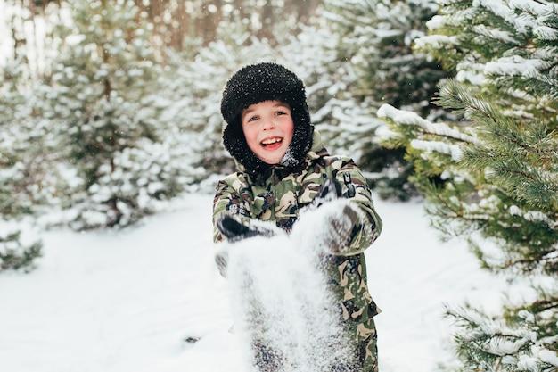 Primo piano sul volto di un ragazzo nella foresta invernale che soffia sul palmo con la neve