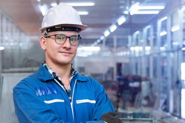 Il viso ravvicinato dell'ingegnere uomo lavoratore è in piedi con fiducia con la suite di lavoro blu