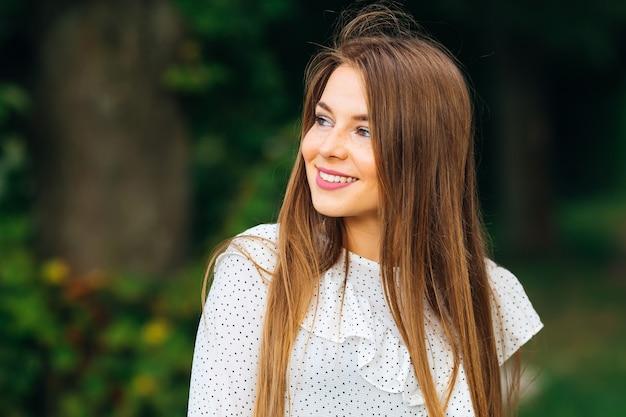 Fronte del primo piano di una ragazza che guarda da parte e sorride magnificamente