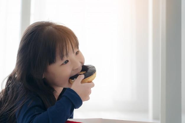 Primo piano del volto della piccola e bella ragazza asiatica affamata che mangia la ciambella al cioccolato, ragazzo carino che mangia la ciambella con la faccia squisita, spuntino del bambino che mangia