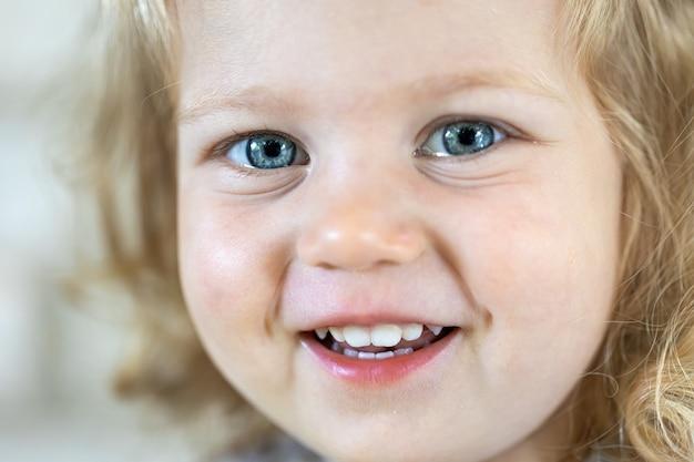 Primo piano volto di una bambina carina con grandi occhi azzurri, ragazza sorridente.