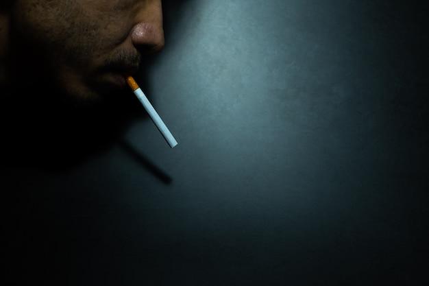 La faccia di primo piano degli uomini sta fumando una sigaretta nell'oscurità scura