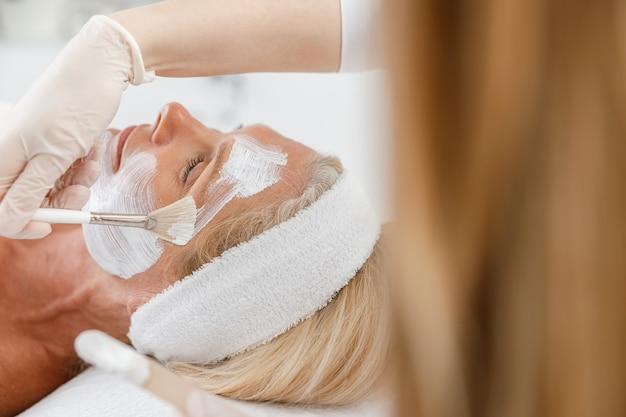 Maschera peeling viso ravvicinata, trattamento di bellezza spa, cura della pelle. senior donna che ottiene la cura del viso dall'estetista al salone della stazione termale.