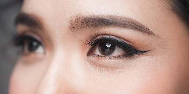 Viso ravvicinato di una bella ragazza con bellissimi occhi, grandi ciglia e sopracciglia