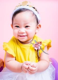 Chiuda sulla piccola neonata della principessa del fronte in vestito bello che è sorriso
