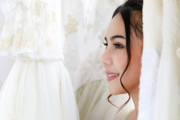 Chiuda sul colpo del viso della giovane sposa felice asiatica bella bella attraente capelli lunghi indossa trucco completo in piedi sorridente da solo scegliendo abito da sposa bianco nello spogliatoio il giorno della cerimonia di matrimonio.