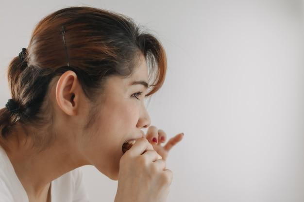 Primo piano volto di donna che morde un pezzo di pane su sfondo bianco