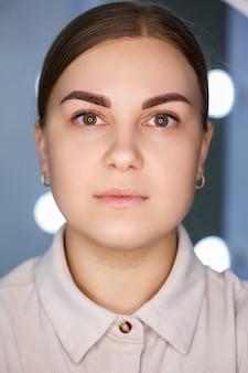 Un primo piano del volto di una giovane donna che ha appena fatto un tatuaggio permanente al sopracciglio.