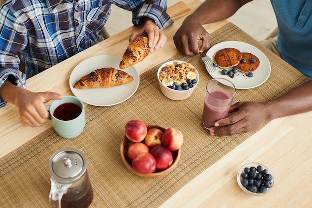 Primo piano della famiglia che mangia frittelle croissant e frutta per la colazione al tavolo a casa