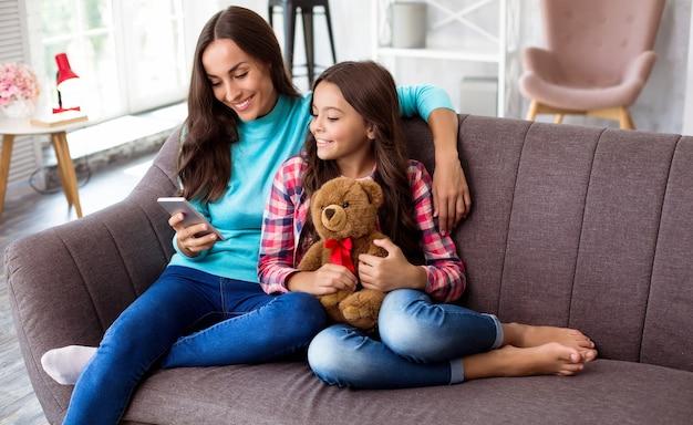 Foto di famiglia ravvicinata di una donna e un bambino con un orsacchiotto seduti insieme su un divano grigio e che leggono qualcosa da uno smartphone