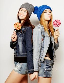 Chiuda sul ritratto di stile di vita alla moda di due giovani ragazze hipster migliori amiche, che tengono caramelle, fanno facce buffe e si divertono.