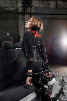 Ritratto alla moda del primo piano di un modello in un corsetto nero e con imbracature in pelle.