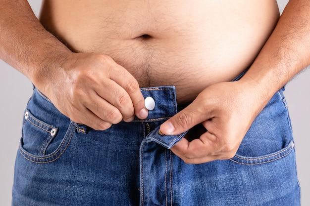 Chiuda in su uomo grasso che cerca di abbottonare i pantaloni