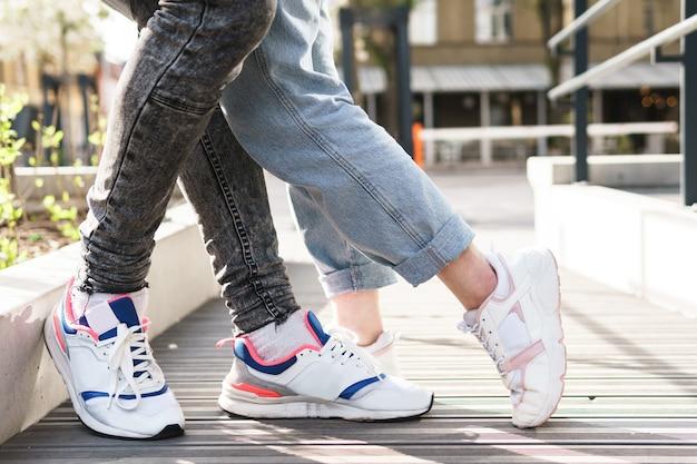 Primo piano dei piedi. coppia che indossa scarpe da ginnastica in un abbraccio.