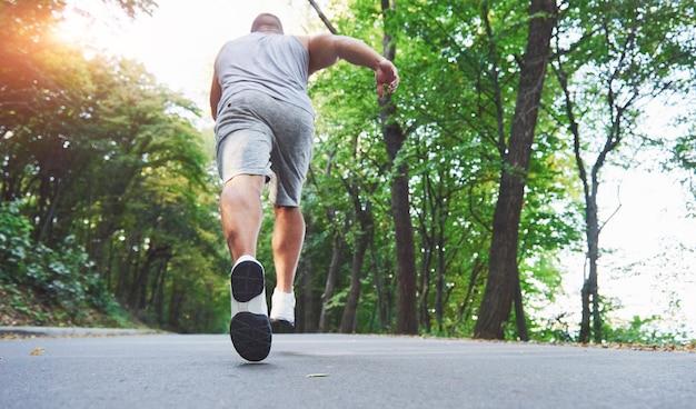 Chiuda in su dei piedi dell'uomo giovane corridore che corre lungo la strada nel parco.
