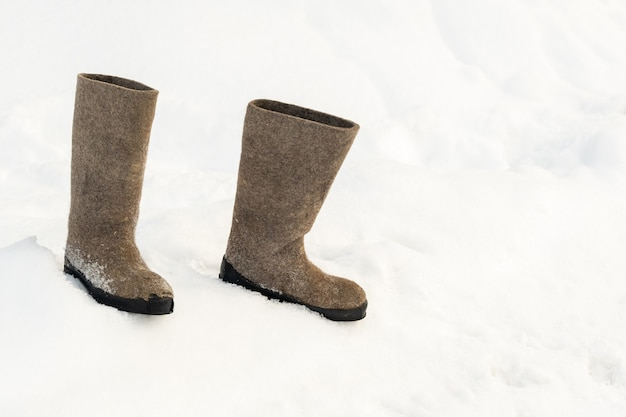 Primo piano di stivali di feltro in piedi nella neve.