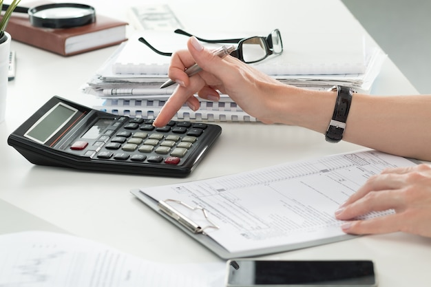 Chiuda in su del ragioniere femminile o banchiere che effettua i calcoli. risparmio, finanze e concetto di economia