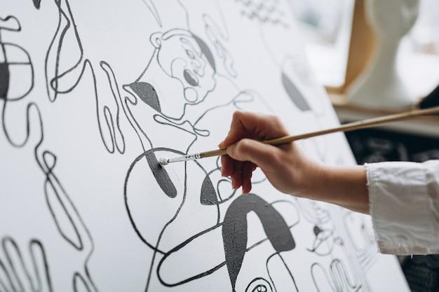Primo piano di un'artista che disegna un'immagine astratta su un cavalletto