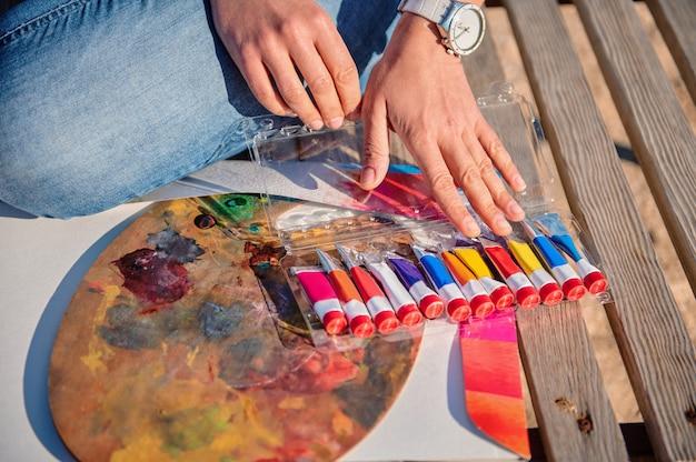 Primo piano delle mani dell'artista femminile su una tavolozza di pittura e tubi con vernici su una superficie di legno