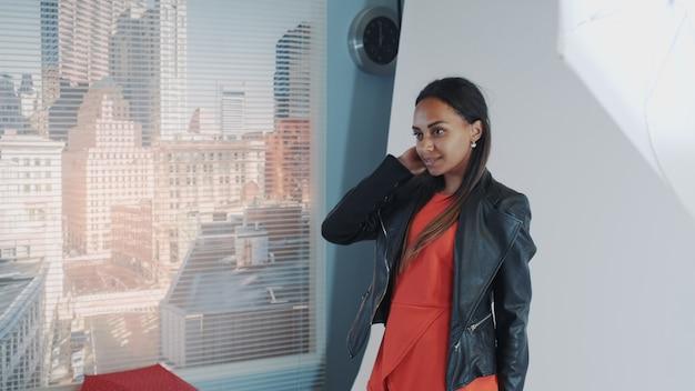 Primo piano dell'assistente femminile che aiuta modello africano a indossare rivestimento durante la sessione di foto in studio